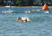 Penny Himes of Elkhart, Indiana (foregraound) looks toward the beach as she completes the swimming leg of the inaugural Little Traverse Triathalon in Harbor Springs, Michigan.  Himes went on the win the overall feamle portion of the competition.