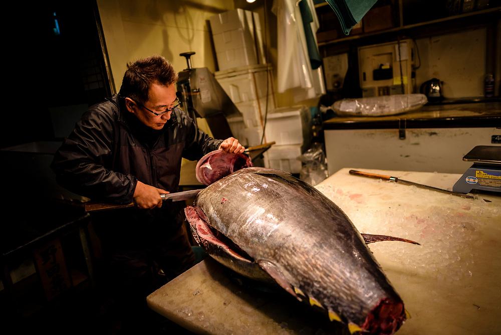 A fishmonger prepares a yellowfin tuna for sale at Yanagibashi Central Market in Nagoya, Japan.