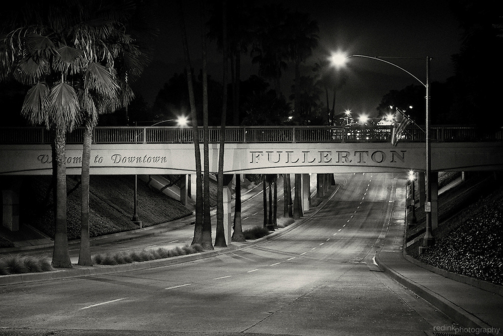 Welcome to Downtown Fullerton sign along train overpass as you enter the downtown Fullerton area along Harbor Blvd. Nightshot. Converted to black and white using Silver Efex Pro.