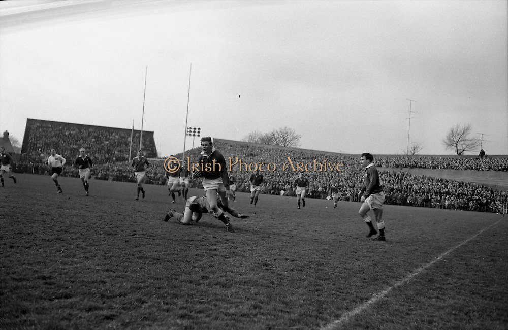 Welsh right wing, SJ Watkins, in possession in mid-field, is tackled by new captain Leahy,.Watkins fell, still in possession but Leahy was injured,..Irish Rugby Football Union, Ireland v Wales, Five Nations, Landsdowne Road, Dublin, Ireland, Saturday 7th March, 1964,.7.3.1964, 7.3.1964,..Referee- A C Luff, Rugby Football Union, ..Score- Ireland 6 - 15 Wales, ..Irish Team, ..F S Keogh, Wearing  Number 15 Irish jersey, Full Back, Bective Rangers Rugby Football Club, Dublin, Ireland,  ..P J Casey, Wearing number 14 Irish jersey, Right Wing, University College Dublin Rugby Football Club, Dublin, Ireland, .. M K Flynn, Wearing number 13 Irish jersey, Right Centre, Wanderers Rugby Football Club, Dublin, Ireland, ..J C Walsh,  Wearing number 12 Irish jersey, Left Centre, University college Cork Rugby Football Club, Cork, Ireland,..K J Houston, Wearing number 11 Irish jersey, Left Wing, Queens University Rugby Football Club, Belfast, Northern Ireland,..C M H Gibson, Wearing number 10 Irish jersey, Stand Off, Cambridge University Rugby Football Club, Cambridge, England, and, N.I.F.C, Rugby Football Club, Belfast, Northern Ireland, ..J C Kelly, Wearing number 9 Irish jersey, Scrum Half, University College Dublin Rugby Football Club, Dublin, Ireland,..P J Dwyer, Wearing number 1 Irish jersey, Forward, University College Dublin Rugby Football Club, Dublin, Ireland, ..P Lane, Wearing number 2 Irish jersey, Forward, Old Crescent Rugby Football Club, Limerick, Ireland, ..T A Moroney, Wearing number 3 Irish jersey, Forward, University College Dublin Rugby Football Club, Dublin, Ireland, ..W A Mulcahy, Wearing number 4 Irish jersey, Captain of the Irish team, Forward, Bective Rangers Rugby Football Club, Dublin, Ireland,  ..M W Leahy,  Wearing number 5 Irish jersey, Forward, University college Cork Rugby Football Club, Cork, Ireland,..E P McGuire,  Wearing number 6 Irish jersey, Forward, University college Galway Rugby Football Club, Galway, Ireland,..M G Culliton, Wearing number 8
