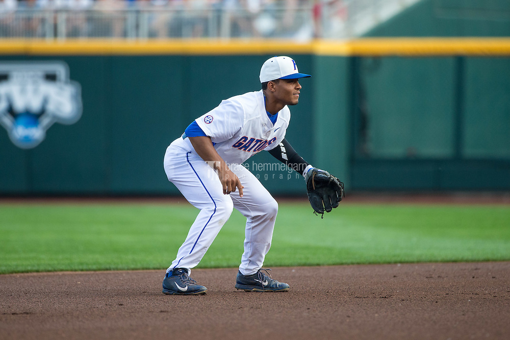 Richie Martin (12) of the Florida Gators fields during a game between the Miami Hurricanes and Florida Gators at TD Ameritrade Park on June 13, 2015 in Omaha, Nebraska. (Brace Hemmelgarn)
