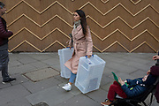 A young woman carrying transparent storage boxes walks past the zigzag battens of a construction hoarding at Notting Hill, on 13th March 2018, in London, England.