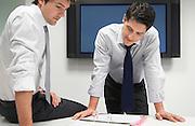 Two Businessmen Looking in File Folder