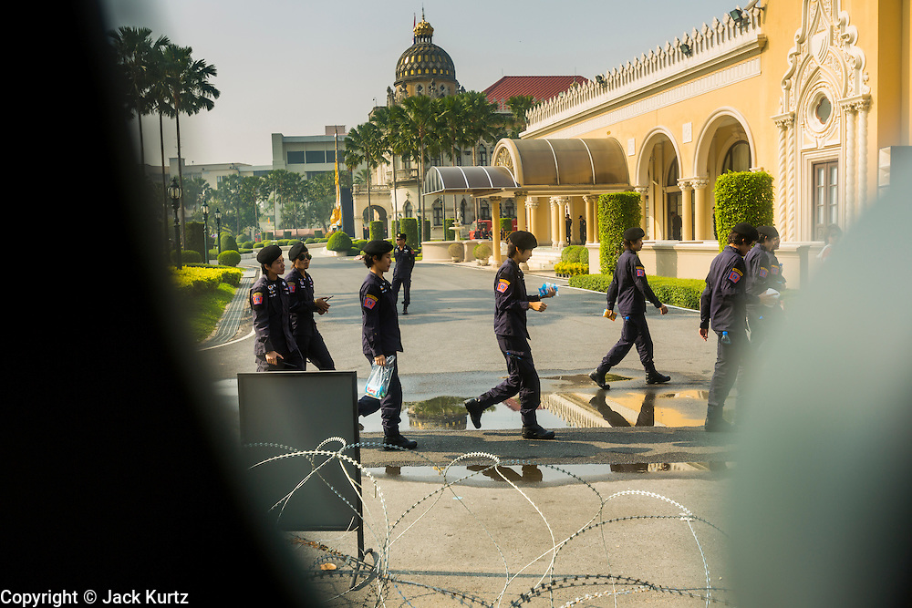 "09 DECEMBER 2013 - BANGKOK, THAILAND: Thai riot police walk past Government House in Bangkok. Thai Prime Minister Yingluck Shinawatra announced she would dissolve the lower house of the Parliament and call new elections in the face of ongoing anti-government protests in Bangkok. Hundreds of thousands of people flocked to Government House, the office of the Prime Minister, Monday to celebrate the collapse of the government after Yingluck made her announcement. Former Deputy Prime Minister Suthep Thaugsuban, the organizer of the protests, said the protests would continue until the ""Thaksin influence is uprooted from Thailand."" There were no reports of violence in the protests Monday.      PHOTO BY JACK KURTZ"