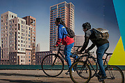 Cyclists pass a regeneration project hoarding at Elephant Park, at Elephant & Castle, London borough of Southwark. Southwark Council's development partner, Lendlease is regenerating over 28 acres across three sites at the heart of Elephant & Castle, in what is the latest major regeneration opportunity in zone 1 London. The vision for the £1.5 billion regeneration is to build on the area's strengths and vibrant character in order to re-establish Elephant & Castle as one of London's most flourishing urban quarters. The Elephant & Castle regeneration is of a scale rarely seen in central London and includes almost 3,000 new homes, plus office, retail, community, leisure and restaurant space.
