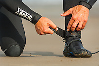 Surfer fastening straps on wetsuit<br /> Whitesands Bay<br /> Near St David's<br /> Surfing<br /> Pembrokeshire<br /> South<br /> Activities and Sports