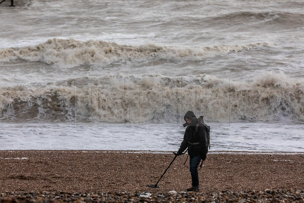 © Licensed to London News Pictures. 17/02/2020. Brighton, UK. A man with a metal detector combs Brighton Beach as waves crash onto the shore as Storm Dennis continues to batter the South Coast with high winds, heavy rain and further risk of flooding. Photo credit: Alex Lentati/LNP
