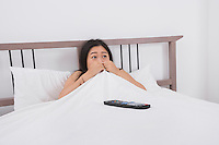 Frightened woman watching TV in bed