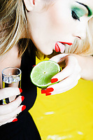one beautiful woman portrait with colorful make-up  and background drinking citrus juice and tequilla shot glass