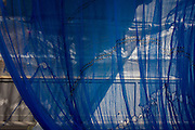 Blue safety netting from a Westminster construction site, blows in the breeze in central London.