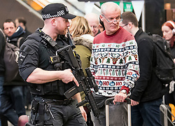 © Licensed to London News Pictures. 23/12/2017. London, UK. Armed police officers watch over as members of the public wait for trains at Euston Station in central London as the Christmas getaway begins. Photo credit: Peter Macdiarmid/LNP