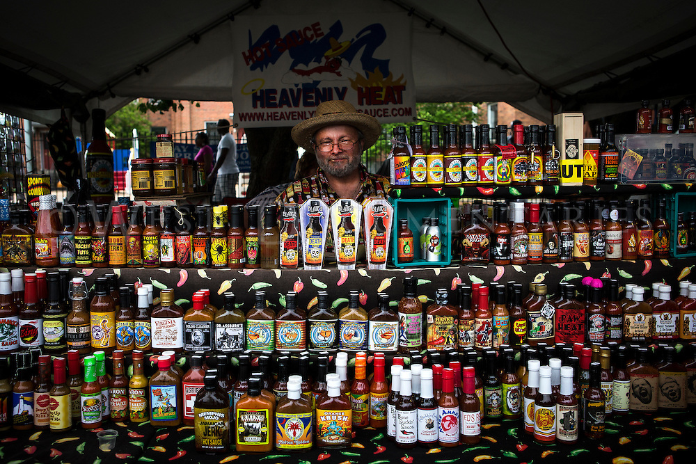 Vendor Drake Lanier, Cheif ChileHead of Heavenly Heat Hot Sauce, from Lexington, N.C., sells over 400 varieties of hot sauces from his concession stand at the Fayetteville Dogwood Festival on April 27, 2013. Photo by John West