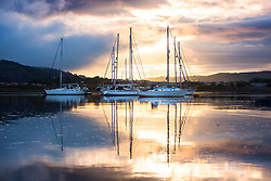 © Licensed to London News Pictures. 17/08/2017. Conwy, UK. Boats reflect into the still water of the River Conwy this morning at sunrise in Conwy harbour, Wales.  Photo credit: Andrew McCaren/LNP