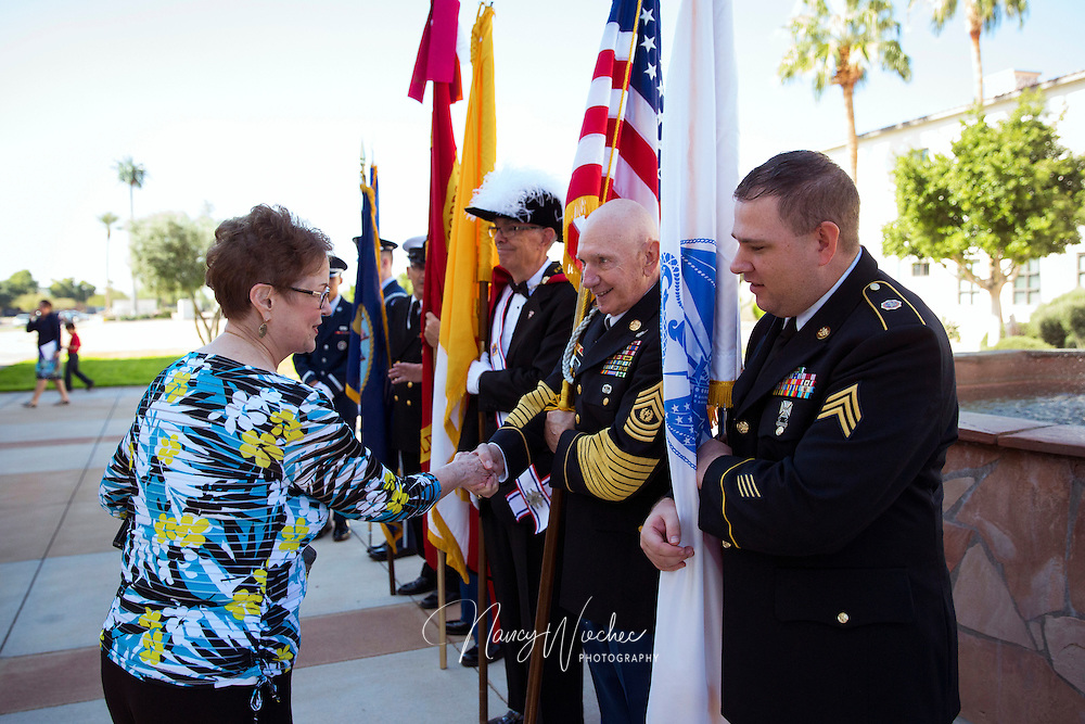A woman greets retired and active service men following the sixth annual Red, White and Blue Mass at St. Thomas Aquinas Church in Avondale, Ariz., Nov. 6. The Diocese of Phoenix marked the occasion to honor active and retired service men and women and to recall those who died in service to the country. (CNS photo/Nancy Wiechec)