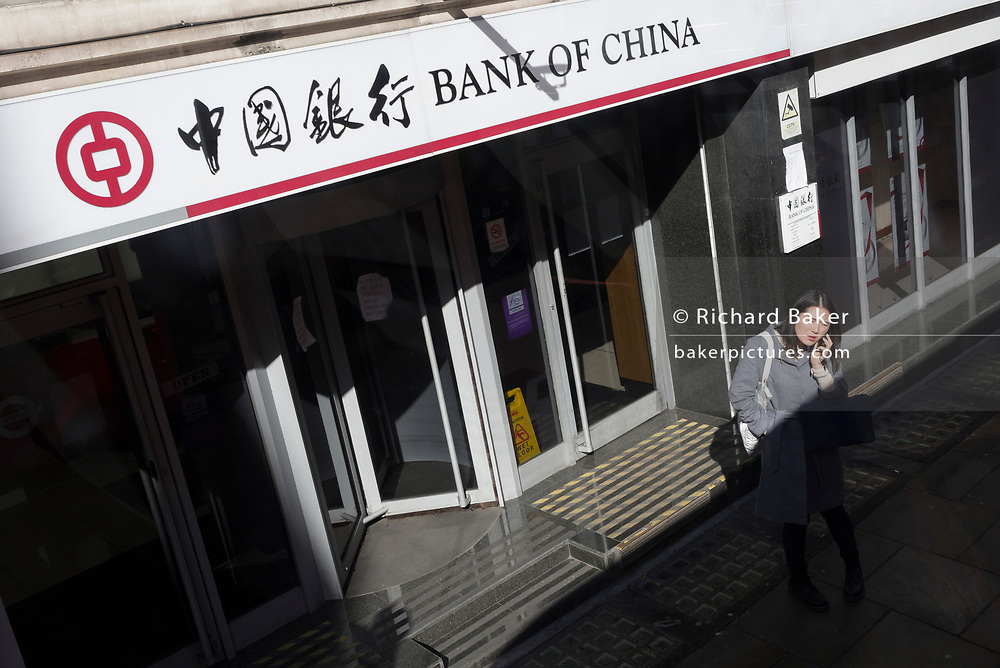 An Asian woman using her mobile phone stands outside the Shaftesbury Avenue branch of the Bank of China in London's West End, on 12th March 2020, in London, England.