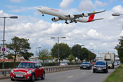 © Licensed to London News Pictures. 29/07/2015. Heathrow, UK. An aircraft coming in to land over a main road and traffic at Heathrow airport. There has been a long running dispute over the expansion and extension of a third runway at the UK's largest airport. A recent report by the Airports Commission recommended that a third runway be built at Heathrow ahead of plans to build a new airport or expand Gatwick. Photo credit : Ian Wylie/LNP