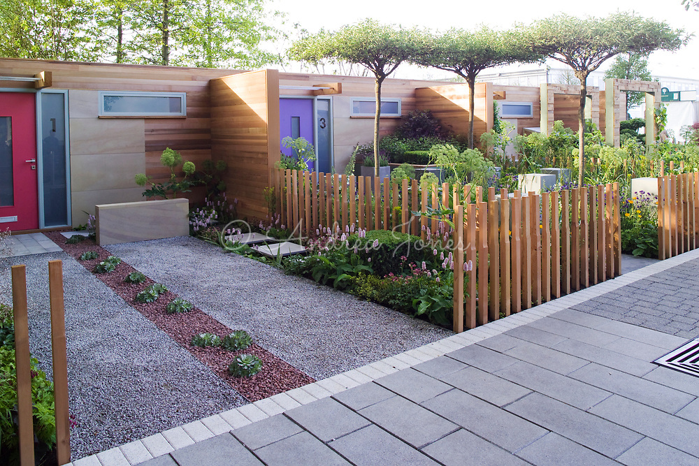 View of the street with porous paving, street furniture, wooden fence stakes, contemporary housing &amp; perennial planting.<br /> The Marshalls Living Street. Design by Ian Dexter (Marshalls). Sponsor Marshalls PLC.