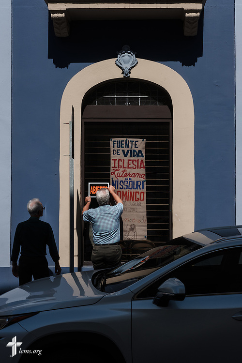 Ramon Cancel affixes an open sign to the exterior of Fuente de Vida (Fountain of Life Lutheran Church), Ponce, Puerto Rico, as Gilberto Valentin assists before worship on Sunday, April 15, 2018. The two Lutherans from Iglesia Luterana Principe de Paz (Prince of Peace Lutheran Church), Mayagüez, Puerto Rico, were visiting for worship. LCMS Communications/Erik M. Lunsford