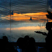ANNA MARIA ISLAND, FL -- July 9, 2009 -- Server Dana Apperson serves dinner against a sunset backdrop at The Sandbar on Anna Maria Island in Manatee County, Fla., on Thursday, July 9, 2009.  (Chip Litherland for The New York Times)