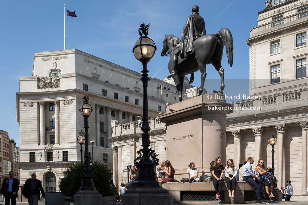 Lunchtime City workers enjoy warm summer sunshine beneath the Duke of Wellington's statue that stands opposite the Bank of England (right) at Bank triangle in the City of London, the capital's financial district (aka the Square Mile), on 22nd August 2019, in London, England.