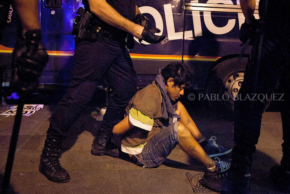 Spanish riot police detaines an 'indignant' protester. Protesters try to gain access to Puerta del Sol Square in Madrid on August 3, 2011, after being evicted in a dawn raid. Hundreds of protesters crammed into each of the sidestreets leading to the central square of Puerta del Sol, birthplace of a nationwide protest against the suffering caused by Spain's economic blight. Lines of riot police crossed their arms and stood in front of the demonstrators, who gathered in swelling numbers in response to Facebook and Twitter pleas for a mass response to their eviction.