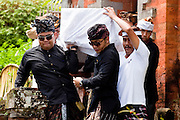 Apr. 25 -- UBUD, BALI, INDONESIA:  Pall bearers bring out the coffin during the funeral for Cokorde Gede Raka, a member of Ubud's royal family Sunday, Apr. 25. Balinese are Hindus and cremate their dead. Balinese funerals are elaborate - and expensive - affairs. A funeral for one person costs a minimum of 45 million rupiah (about $5,000 US). The body is placed into the bull's body at the cremation and cremated in the bull. The funeral pyre is burnt adjacent to the bull. That is what a family may earn in two to three years. The result is that only the rich can afford formal cremations. The body (in the casket) is placed in the top of the funeral pyre and the procession takes the body to the cremation site. The funeral pyre, and the body, are spun at intersections to confuse the spirits so the soul doesn't try to return to its home and to confuse evil spirits.    PHOTO BY JACK KURTZ