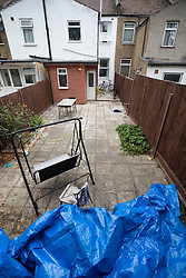 NOTE TO EDITORS : IMAGE TAKEN FROM A SUPERMARKET CAR PARK © Licensed to London News Pictures. 19/07/2019. London, UK. Plastic sheeting covers an area next to burnt timbers in the back garden of a house where it is reported that the body of a woman was found on fire in Chadwell Heath, East London. Fire fighters arrived at the house and then called in the police when they found the woman. Photo credit: Peter Macdiarmid/LNP