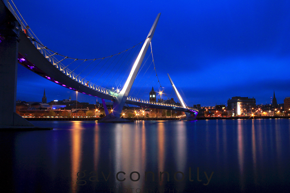 Peace Bridge ,Derry ,Ireland .Blue hour ,I had to grab this in summer time and wait for the right tidal flow to coincide with the blue hour that also gave me an hour before the first train left on sundays .By crossing the tracks was the only way to get onto the silt bed on the convex side of the river when the tide was at its lowest for the season .5 visits and every one of them different due to the current of the river .Dali lama has this on his wall ,chuffed with that .
