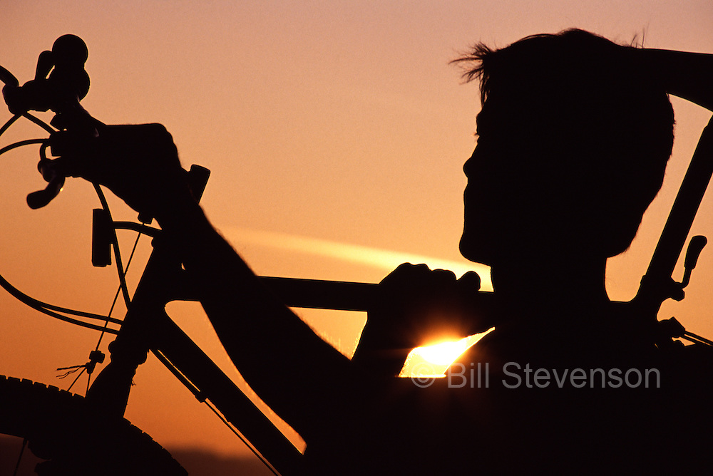 A silhouette photo of a man mountain biking at Smith Rock, OR. He is carrying the bike as the setting sun appears over his shoulder.