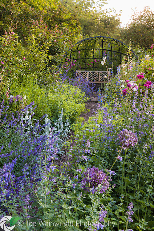 A beautiful border filled with fragrant roses and colourful herbaceous plants at Dorothy Clive Garden, Staffordshire‬.  Photographed in June.