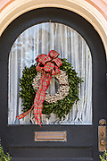 The wooden doorway of a historic home decorated with a popcorn berry Christmas wreath on Meeting Street in Charleston, SC.