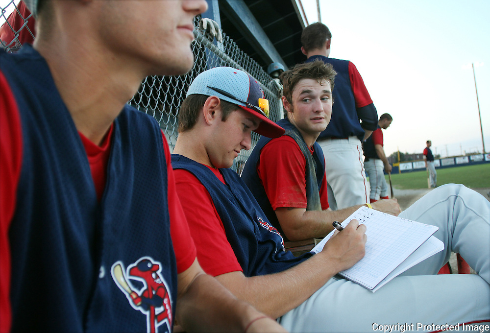 When not in the lineup, Clarinda A's players keep score from the team's dugout.  Holding the scorebook is pitcher Lee Tackett.  To his left is Spencer Messmore.  photo by David Peterson
