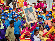 """23 JUNE 2015 - MAHACHAI, SAMUT SAKHON, THAILAND: A man getting off a fishing boat carries a portrait of Princess Maha Chakri Sirindhorn, the Crown Princess of Thailand, at the City Pillar Shrine procession in Mahachai. People get off a fishing boat during the procession for the City Pillar Shrine in Mahachai. The Chaopho Lak Mueang Procession (City Pillar Shrine Procession) is a religious festival that takes place in June in front of city hall in Mahachai. The """"Chaopho Lak Mueang"""" is  placed on a fishing boat and taken across the Tha Chin River from Talat Maha Chai to Tha Chalom in the area of Wat Suwannaram and then paraded through the community before returning to the temple in Mahachai.   PHOTO BY JACK KURTZ"""