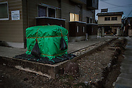 Decontamination began within Fukushima City in 2012 in areas determined to be the most contaminated districts in Fukushima City.  However, in districts consider less contaminated, the work only began in autumn 2015.  Under the green tarpaulin are either one or several flexible black plastic bags which hold approximately 1.5 tons of soil.  The bags cost ¥15,000 (roughly US$128.00).