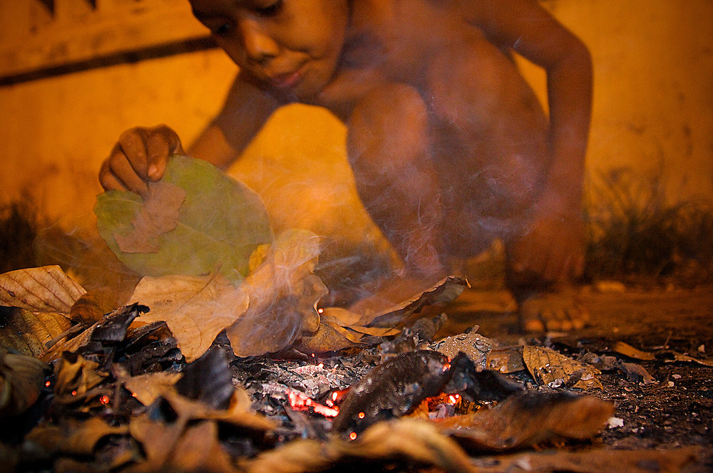 A young homeless boy makes a fire from leaves, without clothes on the street side in Siem Reap, Cambodia 2008