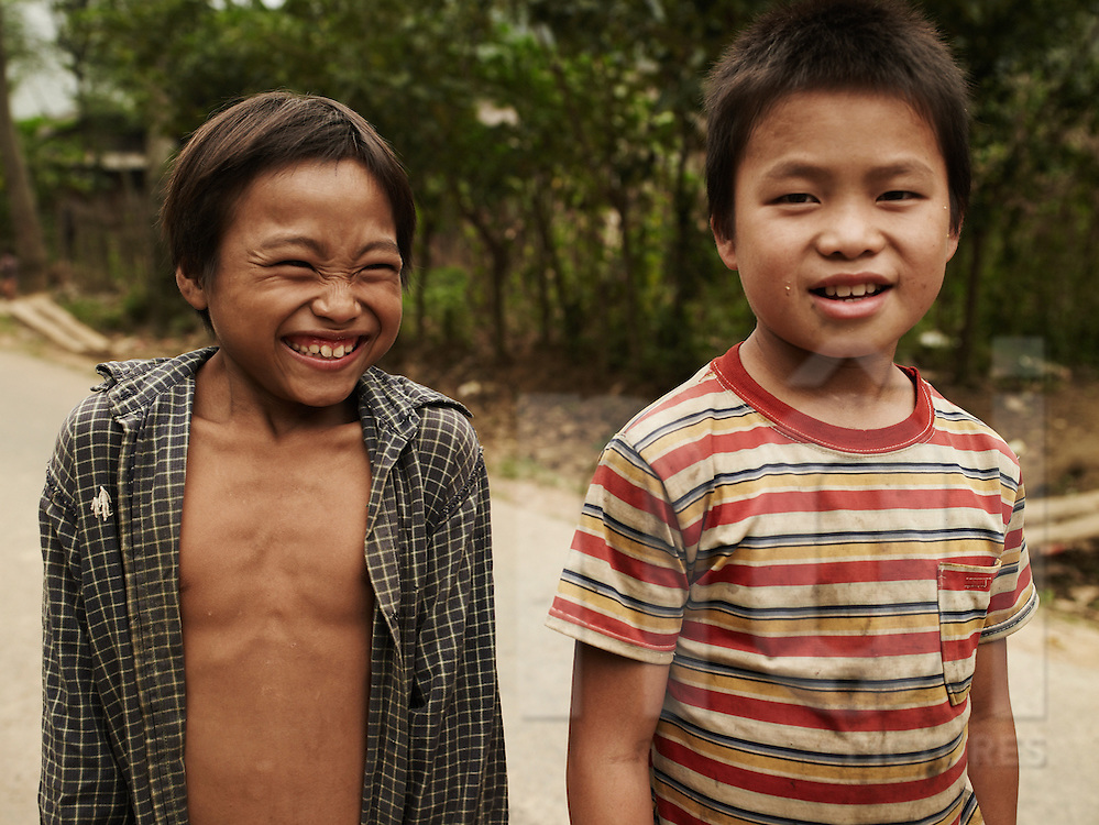 Portrait of two kids standing on the roadside in Ha Giang Province. One laughs while the other looks at the camera. Northern Vietnam, Southeast Asia