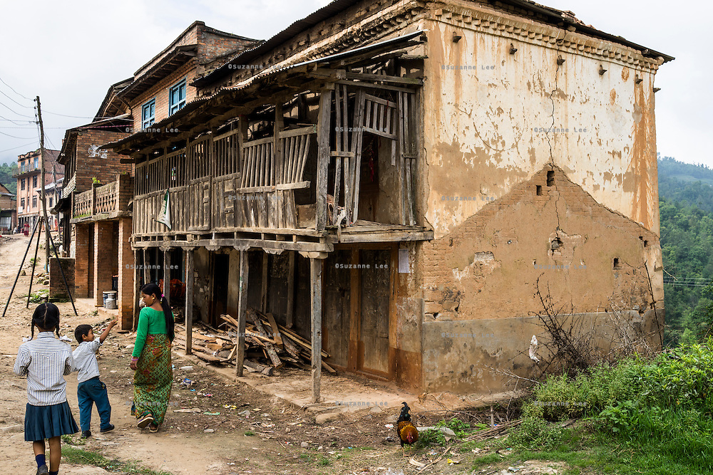 Kalpana Tamang (40), returns to the damaged house where they used to live with her younger daughter Binita (10) and son Sonam (7) to collect items in Kavre, Bagmati, Nepal on 30 June 2015.  Kalpana, a widow with 3 children, has been supported by SOS Children's Villages for many years now and had receive the Home-in-a-Box after the earthquake destroyed her house, almost killing her two daughters. She now lives in a temporary shelter, sharing her dwelling with farm animals, and is trying to make ends meet by weaving bamboo baskets to supplement the financial assistance provided by SOS Childrens Villages. The NGO mostly supports her children's welfare and schooling as well as provides her with essential household and schooling items like kitchen utensils and school books and uniforms. Photo by Suzanne Lee for SOS Children's Villages