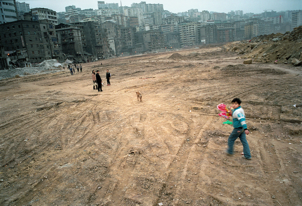Recent settlers from the new city returning home after a visit to the banks of the river. In the foreground the old city of Fuling has been razed and the land reclaimed to protect it from the rising waters to come. The row of darker buildings are what is left of the old city. Higher up in the distance the strip of lighter buildings is where the new city is. China. 2003.