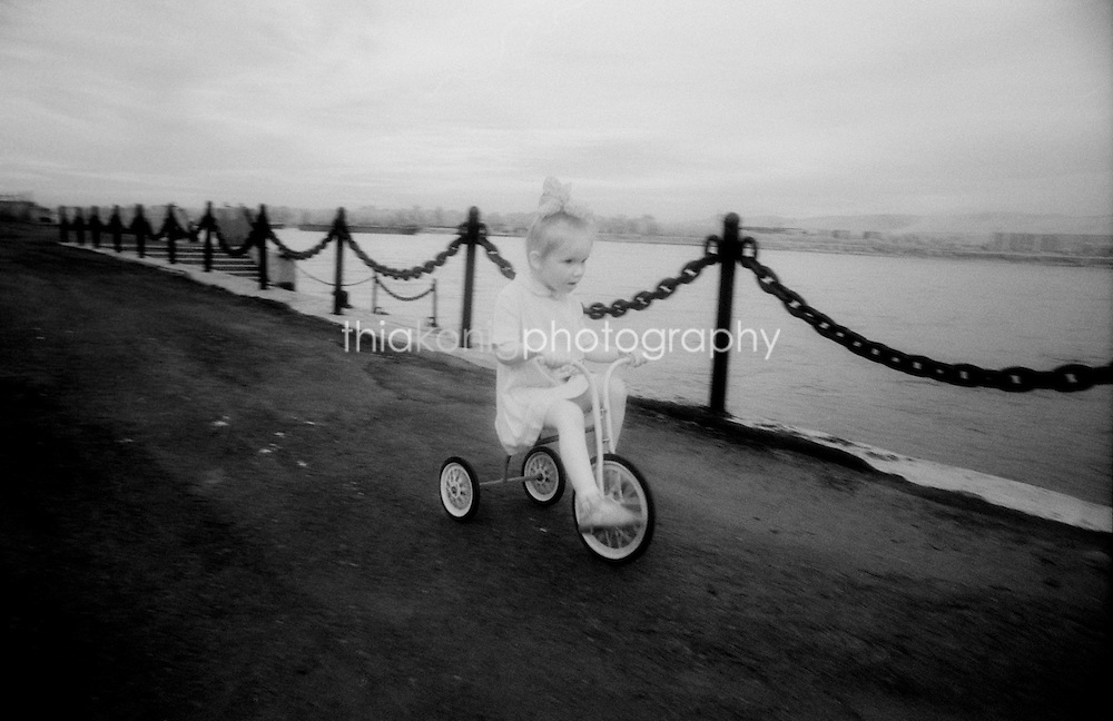 Black and white infrared image of little girl on tricycle along the river in Krasnoyarsk, Siberia, Russia