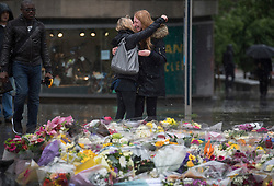 © Licensed to London News Pictures. 06/06/2017. London, UK.  Nicola Smith ( right) the ex-girlfriend of attack victim James McMullan, is comforted by her sister as they stand over flowers at London Bridge, left for those who lost their life in a terrorist attack on Saturday evening. Three men attacked members of the public  after a white van rammed pedestrians on London Bridge.   Ten people including the three suspected attackers were killed and 48 injured in the attack. Photo credit: Ben Cawthra/LNP