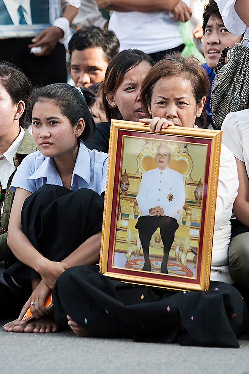 Mourners waiting for the body of former King Norodom Sihanouk to arrive in the Cambodian capital Phnom Penh following his death in exile at the age of 89 years. Grieving Cambodians wore white shirts with black ribbons, and flags flew at half-mast after the news of his death.