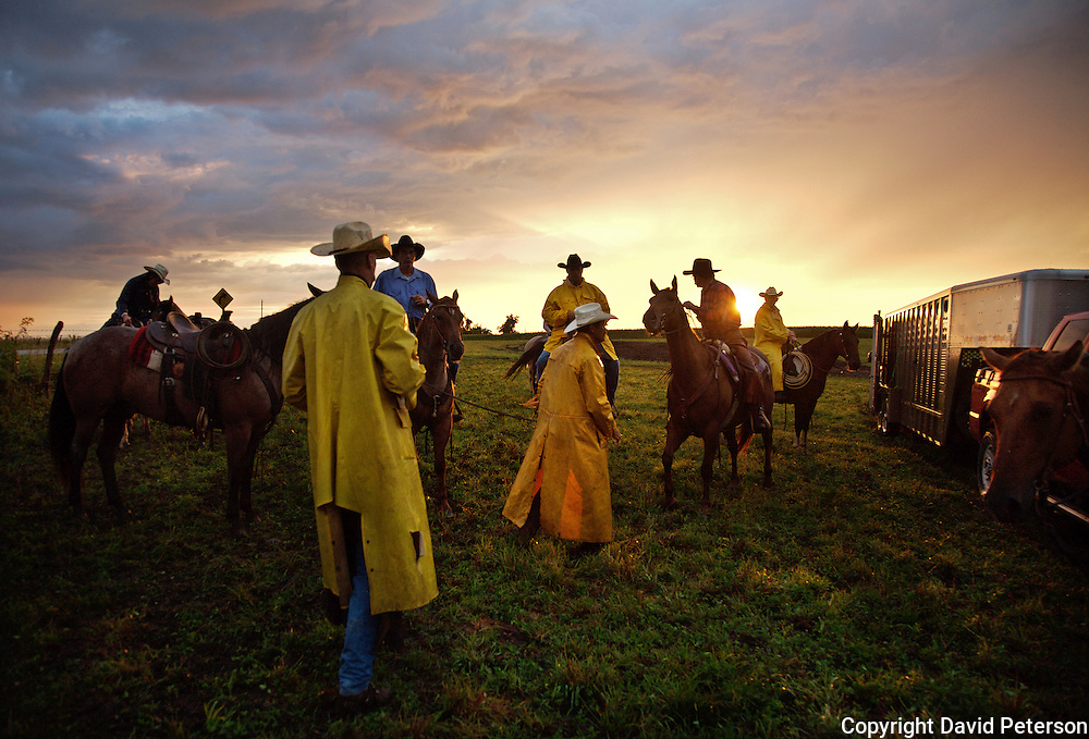 At sunrise, cowboys get ready for a bi-annual roundup at the Bar B ranch near Albia, Iowa,  where calves will be rounded up for bi-annual vaccinations, branding, the implant of growth stimulants, and in some cases, castration.  A morning shower brought out yellow raincoats and turned the ground into a muddy quagmire, making the task more difficult.  Ranch owner Catherine Bay runs the operation with a herd of over 2,000 cattle.