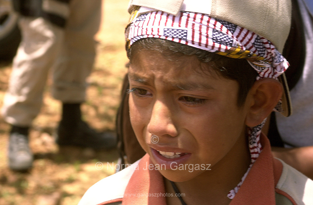 A 6-year-old boy reacts after he, his mother, and other relatives are apprehended by the U. S. Border Patrol agents near Little Tucson, east of Sells, Arizona, on the Tohono O'odham Nation, a 2.5 day walk through the Sonoran Desert in temperatures exceeding 100 degrees.  The group crossed illegally into the U. S. from Mexico and was headed to Los Angeles to work.