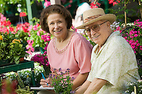 Senior Couple sitting among flowers at plant nursery portrait