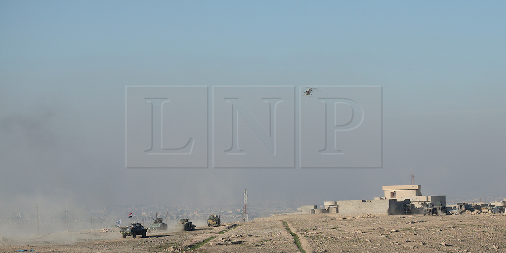 Licensed to London News Pictures. 20/02/2017. Albu Saif, Iraq. With an Iraqi Army Aviation attack helicopter flying overhead Iraqi Security Forces reinforcements move into the village of Albu Saif as part of the ongoing offensive to retake western Mosul from the Islamic State.<br /> <br /> The settlement of Albu Saif is located on high ground overlooking Mosul Airport and as such is a strategic point that needs to be taken as part of the operation to retake the western side of Mosul. Photo credit: Matt Cetti-Roberts/LNP