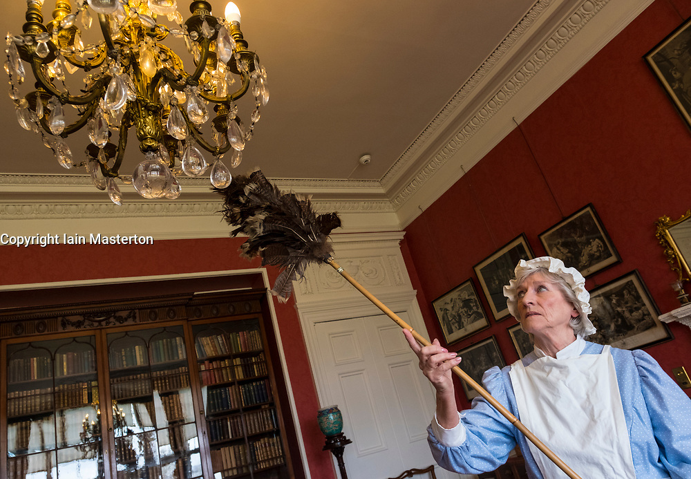 Edinburgh, Scotland, United Kingdom . 27th February, 2018. Volunteers wearing Edwardian costumes prepare to give Lauriston Castle in Edinburgh a Spring clean in preparation for the public opening later in the year. Pictured, Linda MacDonald cleans chandelier with feather duster.