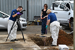 © Licensed to London News Pictures. 16/05/2017. London, UK. Police photograph a hole, excavated by a search team using digging equipment, as the search continues for the body of murdered schoolgirl Danielle Jones at a block of garages  in Stifford Clays in Thurrock, Essex. The 15-year-old was last seen on Monday June 18 2001 at about 8am when she left her home in East Tilbury to catch the bus to school.  Photo credit: Ben Cawthra/LNP