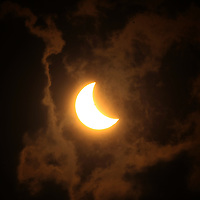 The solar eclipse passes behind a bank of clounds as it begins to  pass over Tupelo on Monday.