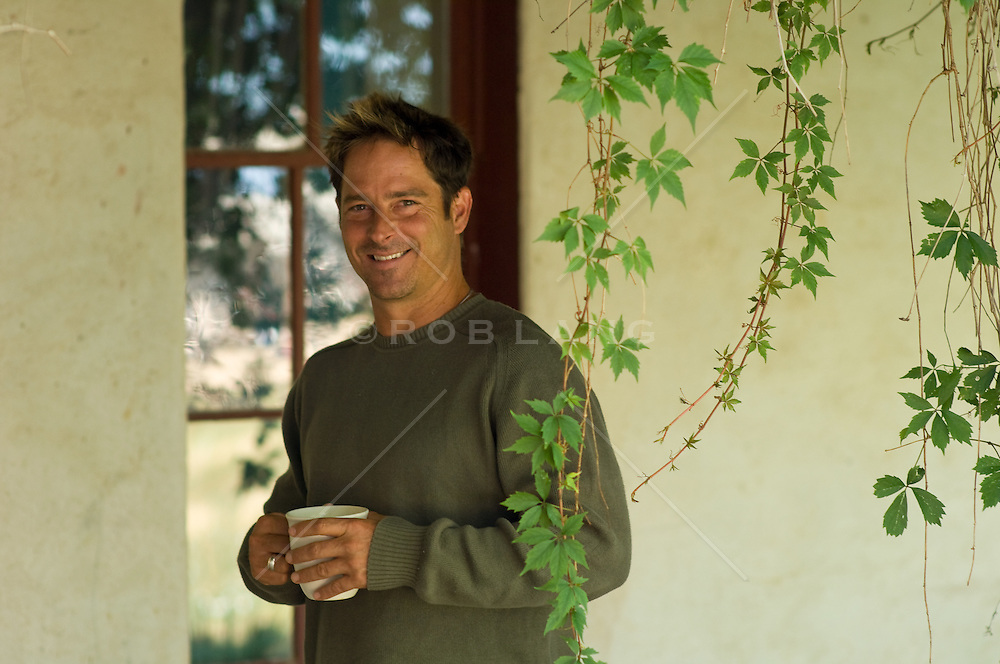 Man in a green sweater holding a coffee cup