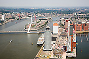 Nederland, Zuid-Holland, Rotterdam-Zuid, 04-07-2006; Kop van Zuid: kop Wilhelminakade, links de ronde toren van het World Port Centre, rechts met wolkenkrabber Montevideo, aan de voet van deze hoogbouw Hotel New York, midden links Erasmusbrug, met daar achter het Noordereiland met Willemsbrug, zicht op de oevers van de Nieuwe Maas, Kralingsche Plas in het verschiet; View on the modern culturadistrict of Rotterdam, Wilhelminakade the World Port Centre (round tower right) and  skyscraper Montevideo, Hotel New York (l),  and in the middle the Erasmusbug (bridge), on the other side of the river Nieuwe Maas. Skyline of the city.. .luchtfoto (toeslag); aerial photo (additional fee required); .foto Siebe Swart / photo Siebe Swart